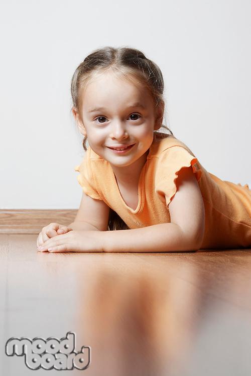 Little Girl Lying on Wood Floor