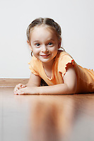 Little Girl Lying on Wood Floor