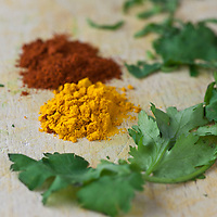 Fresh coriander leaves with small piles of Garam Masala and curry powder on a cutting board.