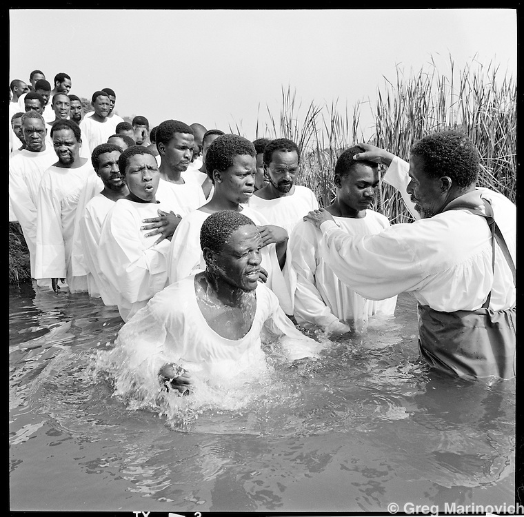 New members of the Nazareth Baptist Church are baptized close to the church headquarters near KwaMashu, KwaZulu Natal, January 1998. The founder Isaiah Shembe is seen as a spiritual descendent of Moses and Jesus, and th church embraces traditional Zulu values and customs. Photo Greg Marinovich