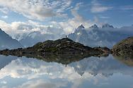 A tourist at Lac Blanc with view on the Aiguille Verte, Grandes Jorasses and Les Aiguilles du Chamonix, Chamonix, France / Impressionen beim Lac Blanc oberhalb von Chamonix, Mont-Blanc, an einem Spätsommertag im September