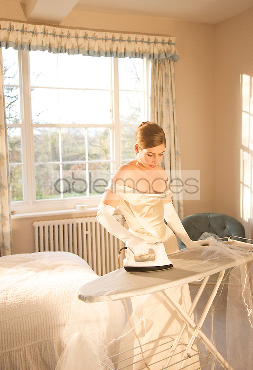 Bride in white wedding gown ironing her veil