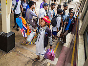 20 MARCH 2015 - PRACHINBURI, PRACHINBURI, THAILAND:  A woman carrying a Thai flag gets off a third class train in Prachinburi. The train was going to Bangkok from Kabin Buri. The State Railways of Thailand (SRT), established in 1890, operates 4,043 kilometers of meter gauge track that reaches most parts of Thailand. Much of the track and many of the trains are poorly maintained and trains frequently run late. Accidents and mishaps are also commonplace. Successive governments, including the current military government, have promised to upgrade rail services. The military government has signed contracts with China to upgrade rail lines and bring high speed rail to Thailand. Japan has also expressed an interest in working on the Thai train system. Third class train travel is very inexpensive. Many lines are free for Thai citizens and even lines that aren't free are only a few Baht. Many third class tickets are under the equivalent of a dollar. Third class cars are not air-conditioned.  PHOTO BY JACK KURTZ