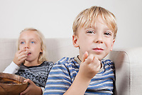 Portrait of young boy with sister watching TV and eating popcorn