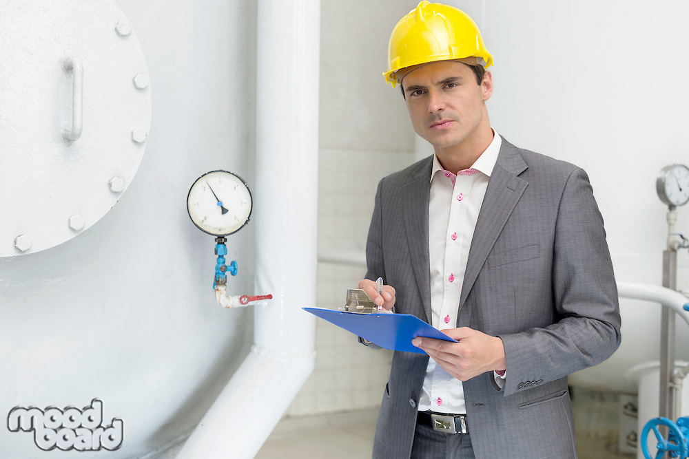 Portrait of confident young male inspector writing on clipboard in industry