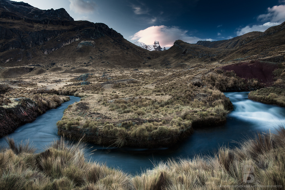 Pastel like colors during sunset of a windy small blue tributary near Lake Viconga with Mt Cuyoc in the background, located in the Cordillera Huayhuash in the Peruvian Andes Mountains.