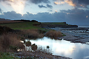 Sunrays through the clouds over the cliffs of Kilve Beach close to sunset, with the pool of the River Holford and Kilve Pill in the foreground.