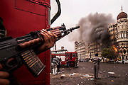 An Indian soldier looks on from cover as firemen rush to tackle the blaze when  a fire re-ignites in theTaj Palace hotel on the morning of 29th November 2008 as the battle for the Taj continues with the terrorists who took it over on the 26th November 2008.<br /> <br /> PICTURE BY SIMON DE TREY-WHITE<br /> + 91 98103 99809<br /> + 91 11 435 06980<br /> +44 07966 405896<br /> +44 1963 220 745<br /> email: simon@simondetreywhite.com photographer in delhi photographer in delhi photographer in delhi
