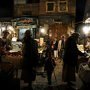 Yemenis eat traditional food outside in the bustling central souq of Old San'aa. UNESCO, the United Nations cultural organization, declared San'a a world heritage site in 1988. San'a was a trade capital as early as the 1st century B.C. With merchants crowded  inside the mud walls of the city, the San'anis built upwards -- as high as nine stories, an impressive feat given the technology of the time. San'aa's homes rest on lower stories built of stone; some date to the 9th or 10th centuries. Over generations, families added floors in brick, making each new floor slightly smaller than the previous one for stability.