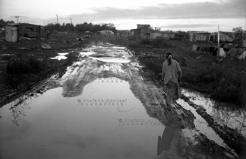 Rome   November 1999.A girl walking along the main street of  the Rom's camp  Casilino 700.