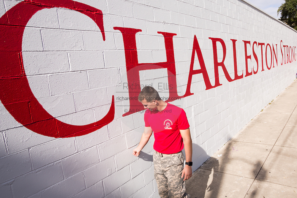 A Citadel Military college cadet walks past the newly painted Charleston Strong wall mural during ceremonies October 21, 2015 in Charleston, South Carolina. The wall is to commemorate the mass shooting at the historic Mother Emanuel African Methodist Episcopal Church last June.