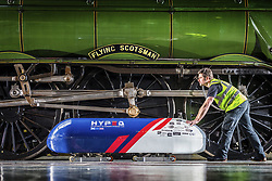 April 26, 2018 - York, Yorkshire, UK - York UK. Jonny Lees moves the UK's first Hyperloop pod into position in front of the Flying Scotsman ahead of a photo call at York Railway Museum this morning. The revolutionary Hyperloop technology could see passenger pods travelling inside near-vacuum tubes at speeds of up to 650 mph and could theoretically reduce York to London journey times to just 20 minutes. The Hyperloop pod is at the museum to launch the museum's new visual identity & to mark the occasion bought together the past, present & future of rail travel. (Credit Image: © Andrew Mccaren/London News Pictures via ZUMA Wire)