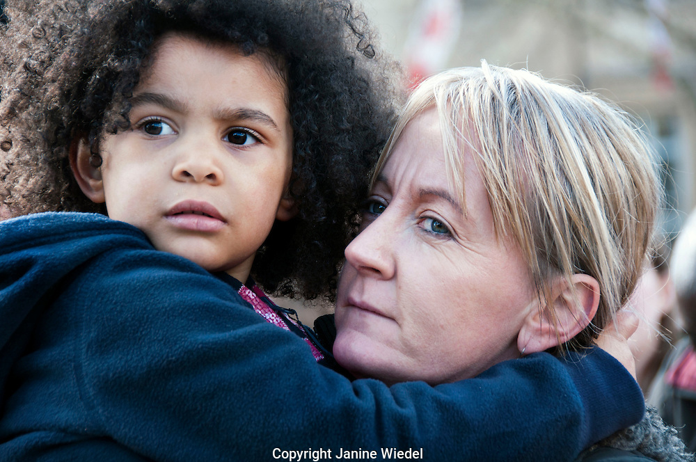 Mixed race mother and child listening to speakers at anti-racism protest