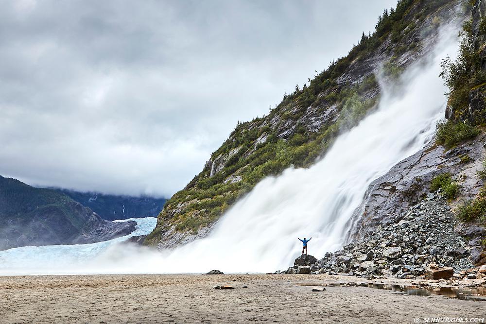 A man stands below Mendenhall Glacier Falls near Juneau, Alaska.