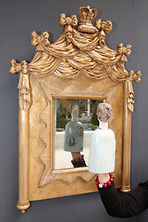 © licensed to London News Pictures. LONDON, UK  08/06/2011. An exhibitor holds a ceramic figure by Jane Muir with William and Kate, the new Duke & Duchess of Cambridge, printed on it in front of a mirror that was owned and used by the first Duke of Cambridge in the 17th Century at the Olympia International Fine Art & Antiques Fair. All 30,000 items on sale from 150 dealers are vetted for authenticity by a panel of experts. The show opens in Olympia tomorrow (Thursday) and runs for 11 days. Please see special instructions for usage rates. Photo credit should read CLIFF HIDE/LNP