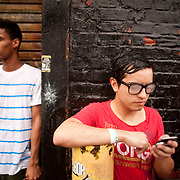 July 29, 2011 - Brooklyn, NY : Juan Forero, right, who is from Colombia, checks his cell phone as he waits in line to enter the House of Vans at 25 Franklin Street in Greenpoint, Brooklyn on Friday night. Acts included the hardcore punk bands the 'Cro-Mags' and 'Fucked Up.' CREDIT: Karsten Moran for The New York Times