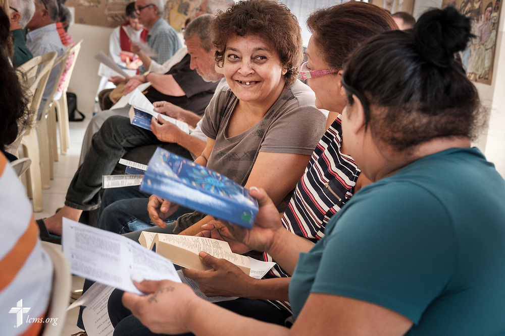 Visitors hand Bibles to each other for worship at Fuente de Vida (Fountain of Life Lutheran Church), Ponce, Puerto Rico, on Sunday, April 15, 2018. LCMS Communications/Erik M. Lunsford