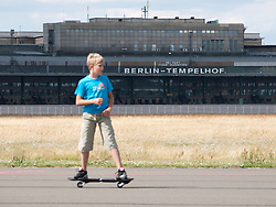 Boy skateboarding along runway at new city public Tempelhofer Park on site of famous former Tempelhof Airport in Berlin Germany