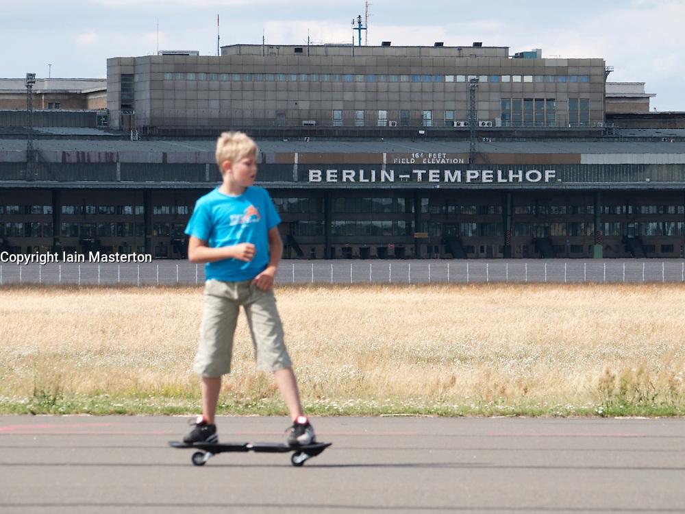 Boy skateboarding along runway at new city public Tempelhofer Park on site of famous former Tempelhof Airport in Berlin Germany