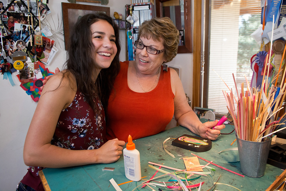 mkb072517a/North/Marla Brose --  Diana Moya-Lujan greets her granddaughter Andrea Torres, 15, inside her home studio in Santa Fe, N.M., Tuesday, July 25, 2017. Moya-Lujan, a straw applique artist , will be showing work at Spanish Market along with Andrea, Moya-Lujan's daughter and three other granddaughters. (Marla Brose/Albuquerque Journal)