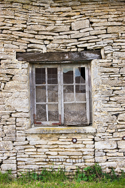 Chicken wire on broken window of old derelict subsiding stone barn , Kelmscott, The Cotswolds, Gloucestershire, UK