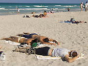 group of young sunbathers sleeping on the beach Miami USA