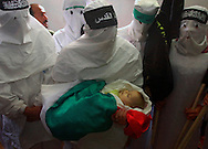 Hamas militants and Palestinian victims-Islamic Jihad militant dressed as suicide bombers  mourn over the body of 4-month-old baby girl Iman Hijo at her funeral in Deir El-Balah in the southern Gaza Strip, Tuesday May 8, 2001. Hijo died instantly when her home in Khan Yunis refugee camp was shelled by Israeli troops responding to mortar fire on nearby Jewish settlements. Israeli Prime Minister Ariel Sharon apologized for the infant's death, the youngest victim in more than seven months of Israeli-Palestinian violence.