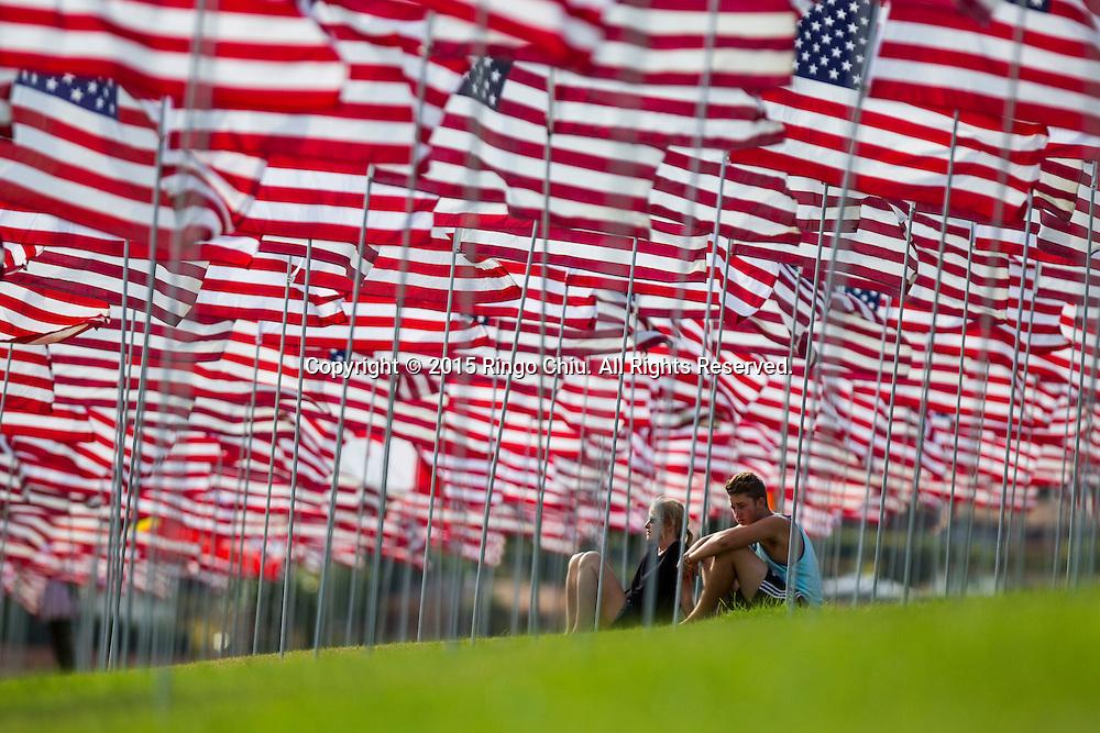 9月10日,在美国加利福尼亚州洛杉矶的马里布,一对男女在旗帜中间休息。当天,在美国&ldquo;9&middot;11&rdquo;事件十四周年前夕,佩珀代因大学的学生和教职员工在学校草坪上插起约3000面美国国旗,纪念&ldquo;9&middot;11&rdquo;事件遇难者。新华社发(赵汉荣摄)<br /> A man and a woman sit on amongst 3,000 US flags are displayed at Pepperdine University to mark the 14th anniversary of the 9/11 terror attack, September 10, 2015 in Los Angeles, California, the United States. (Xinhua/Zhao Hanrong)Photo by Ringo Chiu/PHOTOFORMULA.com)
