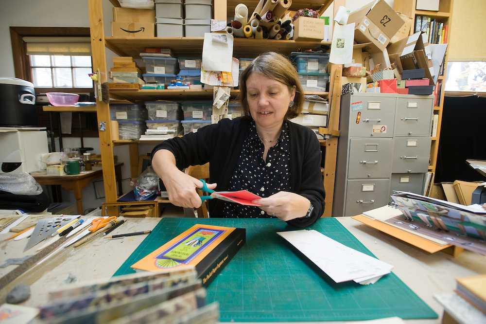 Woman cutting paper for a pop-up book in her art studio
