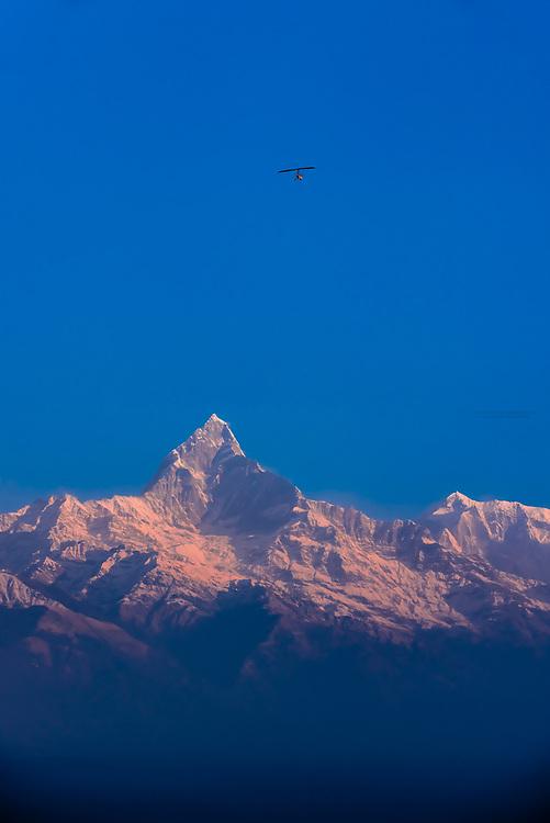 An ultralight aircraft approaches Machapuchare (Fishtail) and Annapurna III, peaks of the Annapurna Massif of the Himalayas, seen from Sarangkot,  near Pokhara, Nepal.