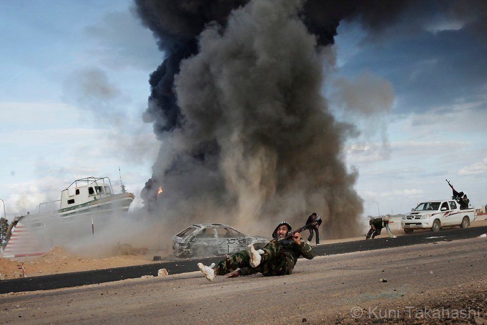 Rebel soldier against Col. Muammar Gaddafi lies on the ground after government force drop shells at the frontline near Ras Lanuf on March 9, 2011. The government military and rebels kept fighting for taking control of the town for the last two days. .Photo by Kuni Takahashi