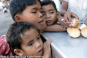 Underprivileged street children prepare to eat bread in Phnom Penh, Cambodia. The World Health Organization states that 39% of Cambodia's nearly 15 million people are malnourished.
