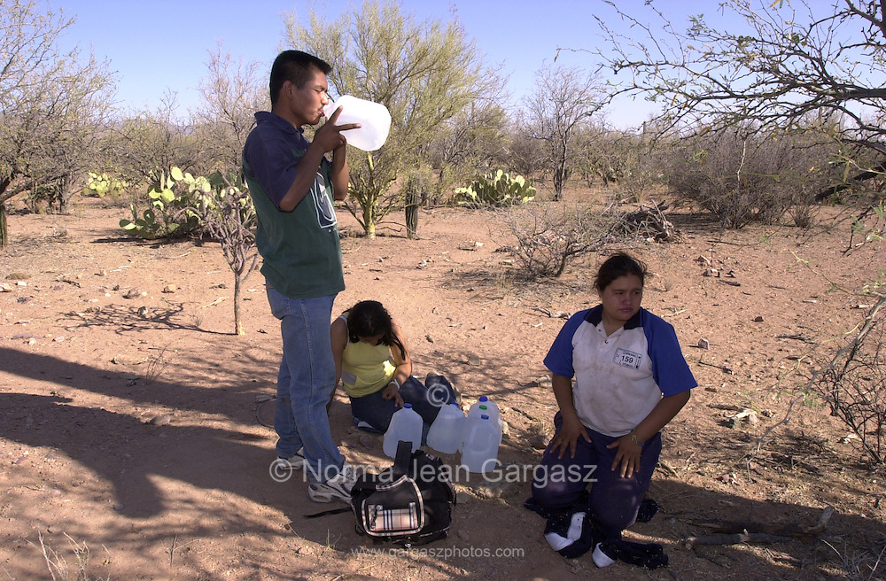 Luis Benitez Ortiz, 19, (left), Sara Ochoa Anarade, 19, and Anai Melchor Ramirez, 20, drink water along a trail south of Sells, Arizona, after crossing illegally in to Arizona, USA, from Mexico.  The three, from Michoacon, Mexico, entered the United States illegally at the Arizona border on to the Tohono O'odham Nation at the deadliest stretch of desert for crossers along the U.S. border with Mexico.  The water was placed along the trail about 18 miles north of the border by Rev. Mike Wilson to help alleviate deaths from dehydration.