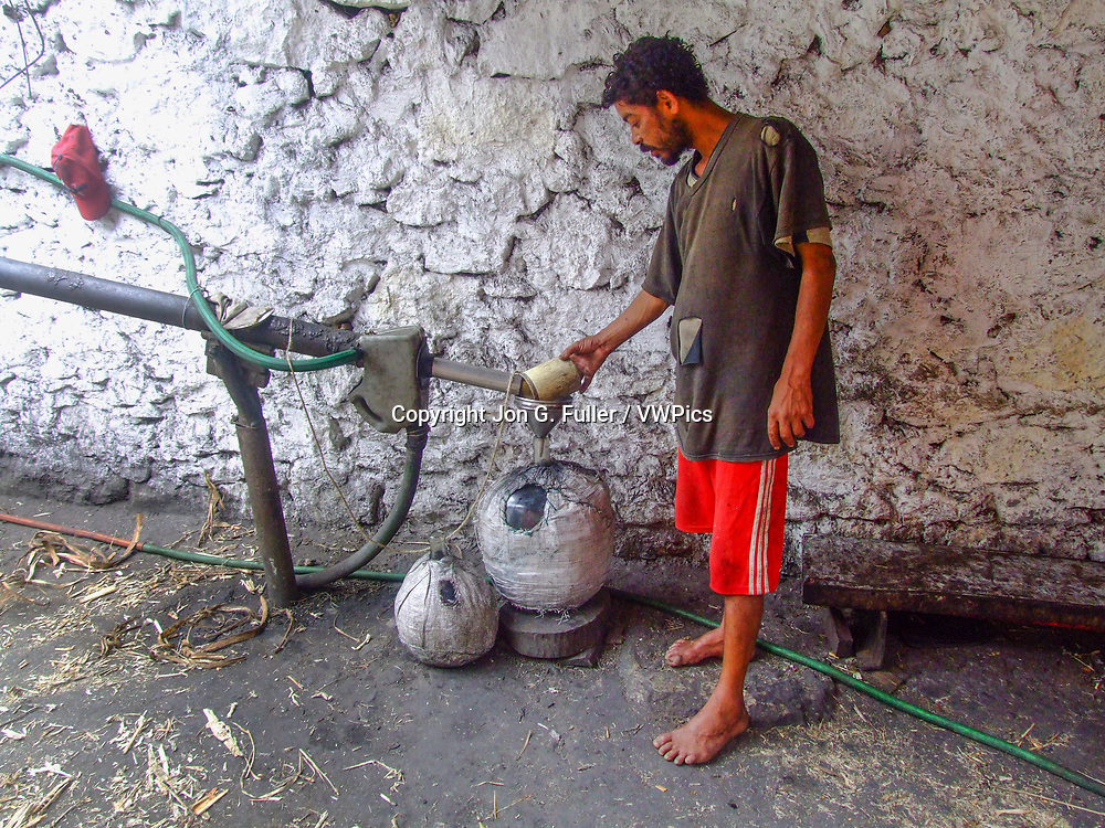 A man distills grogue, a local alcoholic liquor, from crushed sugar cane.  Valley of Paul, Santo Antao, Republic of Cabo Verde, Africa.