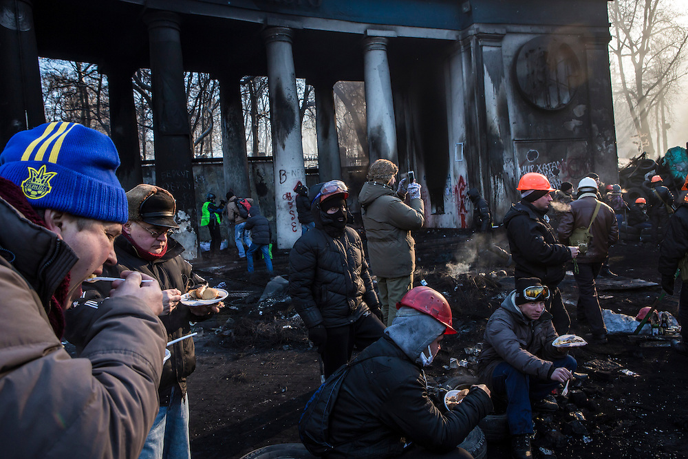 KIEV, UKRAINE - JANUARY 24: Anti-government protesters eat lunch near Dynamo stadium, the site of the fiercest recent clashes with police, on January 24, 2014 in Kiev, Ukraine. After two months of primarily peaceful anti-government protests in the city center, new laws meant to end the protest movement have sparked violent clashes in recent days. (Photo by Brendan Hoffman/Getty Images) *** Local Caption ***