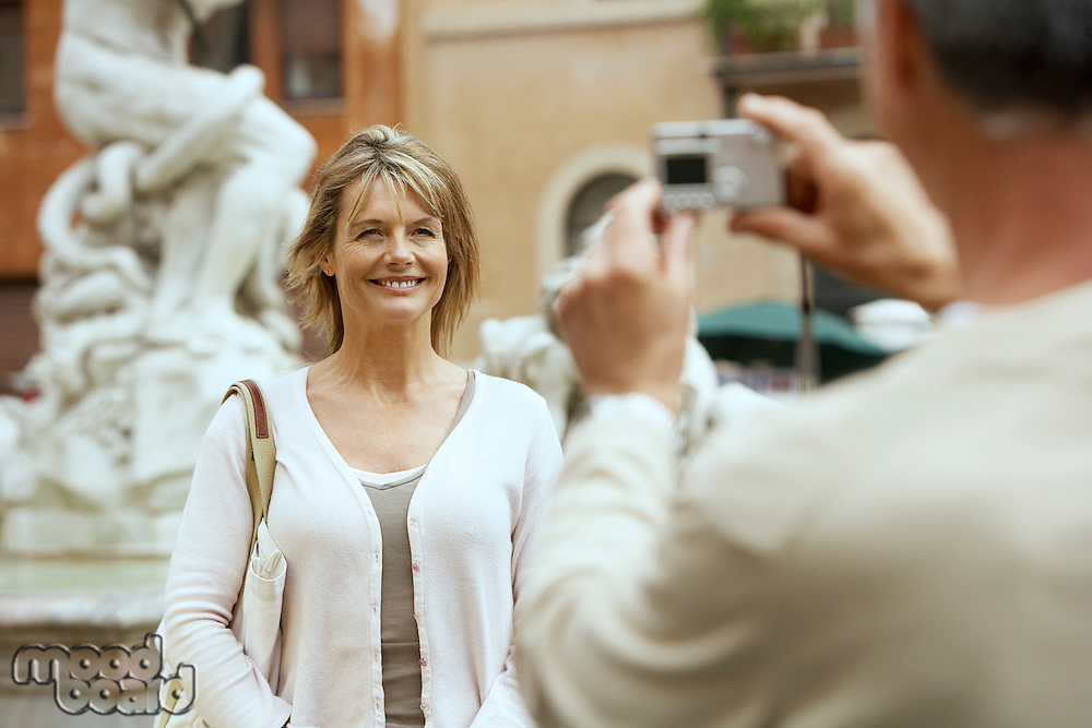 Man photographing partner by statue in Rome Italy focus on woman