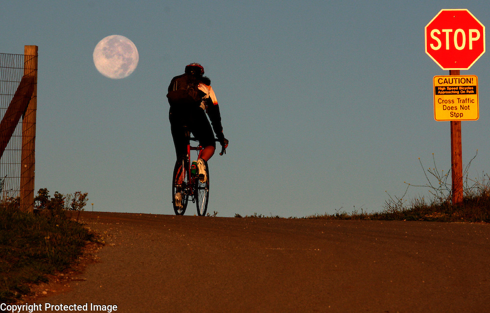 The first rays of sunrise illuminate a cyclist heading up the Great Meadow bike path at UC Santa Cruz as the full moon sets early on Tuesday November 3, 2009.
