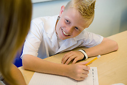 Teenager boy in class smiling,