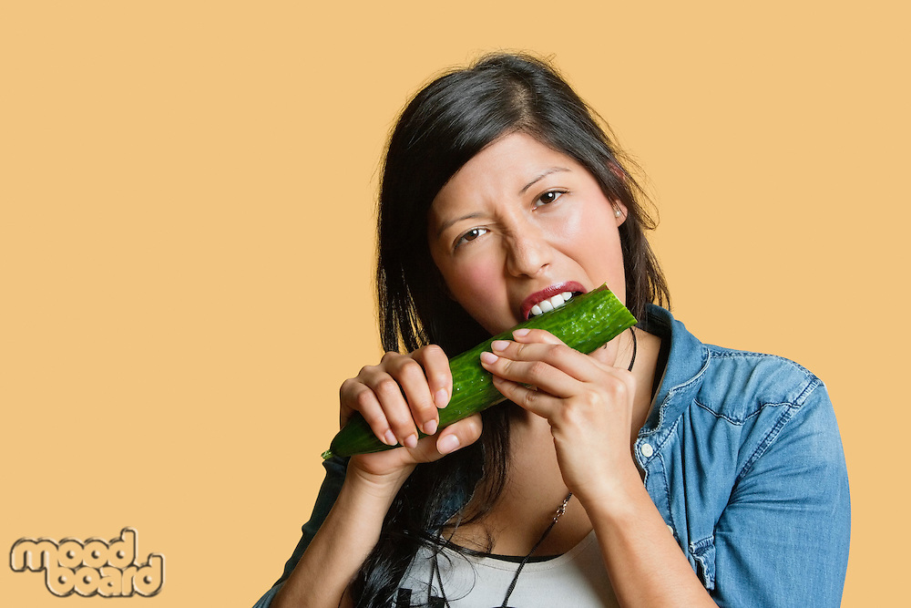 Portrait of a young woman eating cucumber over colored background