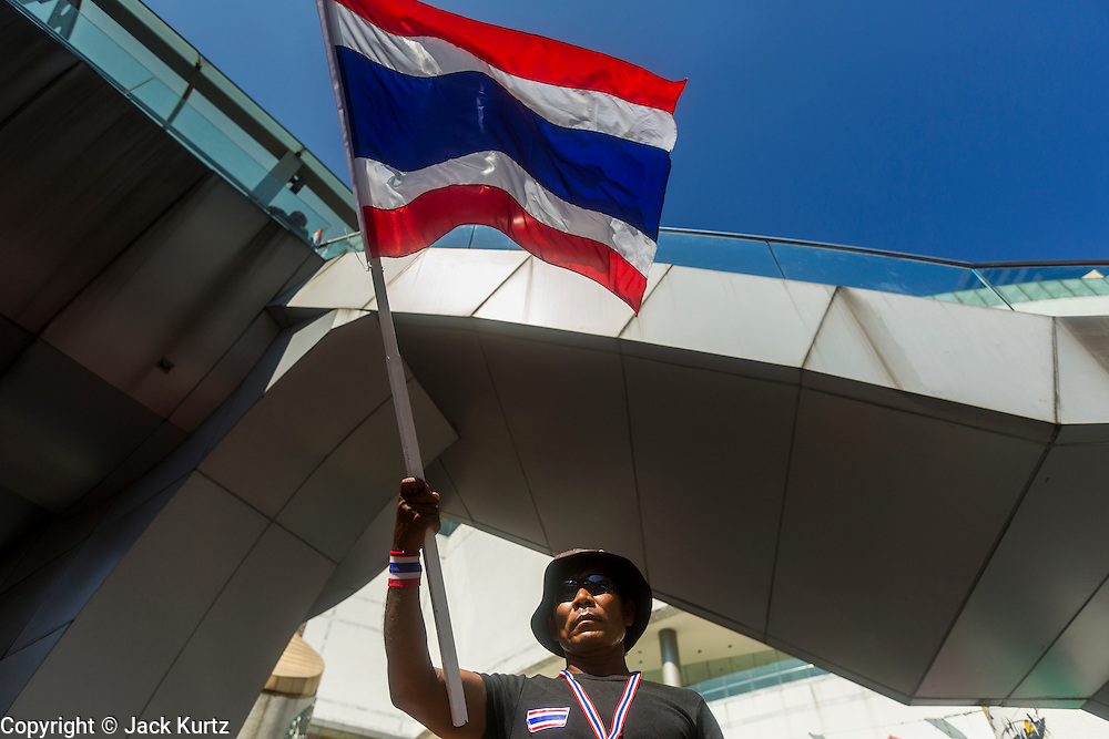 """13 JANUARY 2014 - BANGKOK, THAILAND:  An anti-government protestor waves a Thai flag across the street from MBK shopping center in Bangkok. Tens of thousands of Thai anti-government protestors took to the streets of Bangkok Monday to shut down the Thai capitol. The protest was called """"Shutdown Bangkok"""" and is expected to last at least a week. The Shutdown Bangkok protest is a continuation of protests that started in early November. There have been shootings almost every night at different protests sites around Bangkok, including two Sunday night, but the protests Monday were peaceful. The malls in Bangkok stayed open Monday but many other businesses closed for the day and mass transit was swamped with both protestors and people who had to use mass transit because the roads were blocked.   PHOTO BY JACK KURTZ"""
