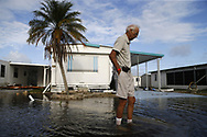 Richard Norwak wades through the water as he tries to check on his house Monday, Sept. 11, 2017, a day after hurricane Irma made landfall in the Holiday Manor area in Naples, Fla.
