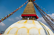 A worker stands next to the Eyes of Buddha on the Boudhanath stupa in Kathmandu, Nepal.