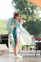 © Licensed to London News Pictures. 18/07/2014. Southwold, UK.   Lily Allen recording a special live performance for the Andrew Marr Show from The Latitude Festival on a riverside stage.   Lily Allen replaced Two Door Cinema Club as tonight's headline act - this was announced earlier this week as a result of Two Door Cinema Club's frontman Alex Trimble's ill health.  It was reported Trimble collapsed at an american airport.  Latitude is British annual music festival.  Photo credit : Richard Isaac/LNP