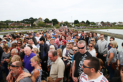 © Licensed to London News Pictures. 29/08/2015. Shoreham, UK.  Thousands of flowers can be seen on the Footbridge where today people holding a minute silence at 1.20pm to remember the 11 confirmed victims of the plane crash of a Hawker Hunter Jet at the Shoreham Airshow on August 22nd, Today August 29th 2015. Photo credit : Hugo Michiels/LNP