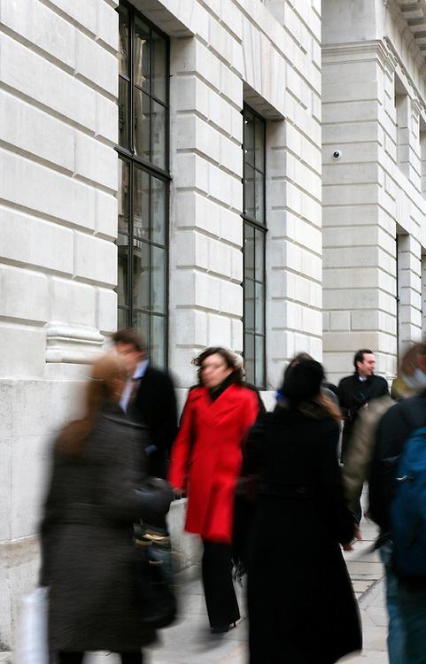 women in red coat walking along pavement past office in fleet street, london amongst lots of other business people in black