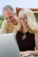 Mature couple using laptop in back yard