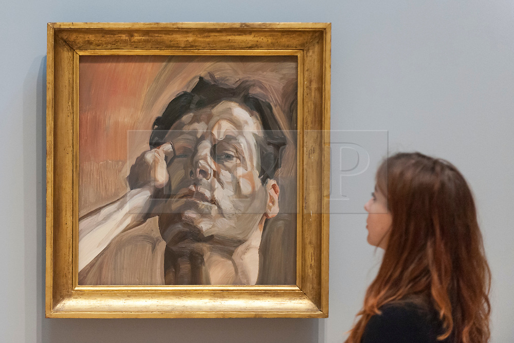 "© Licensed to London News Pictures. 26/02/2018. LONDON, UK. A staff member views ""Man's Head (Self Portrait II)"", 1963, by Lucian Frejd Preview of ""All Too Human"", an exhibition at Tate Britain which explores how artists in Britain have stretched the possibilities of paint in order to capture life around them.  The exhibition runs 28 February to 27 August 2018 and includes rarely seen works by Lucian Freud and Francis Bacon.  Photo credit: Stephen Chung/LNP"