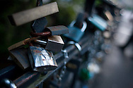 Locks on a bridge over a channel in Vilnius, Lithuania are etched with the names of couples.