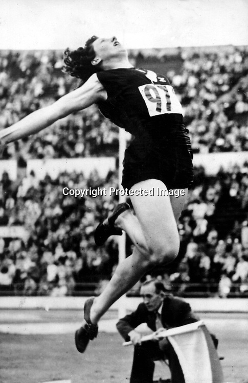 Athletics archive. Yvette Williams jumps her way to an Olympic Gold medal with a jump of 6.24m. Helsinki Olympic Games, 1952. Photo: PHOTOSPORT