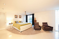 Partly carpeted bedroom with matching leather armchairs